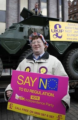 With the clearly ridiculous Nigel Farage on yet another of his childish  stunts showing off by climbing into an APC standing parked on a trailer!